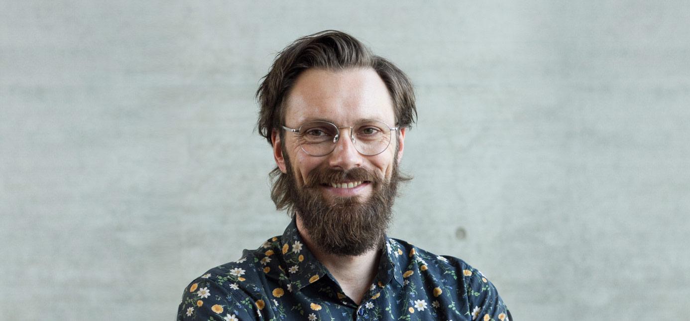 Ein Portrait von Dr. Michael Kirchler vor einem neutralen grauen Hintergrund.